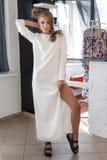 Schöne sexy junge Frau im schönen modernen weißen Kleid im Studio, das für das Kameramodetrieb für die Kleidung aufwirft Lizenzfreie Stockfotografie