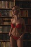 Schöne sexy langhaarige blonde Frau in der roten Wäsche, die im Innenraum aufwirft Lizenzfreie Stockbilder