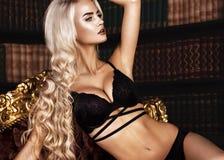 Schöne sexy langhaarige blonde Frau in der schwarzen Wäsche, die im Innenraum aufwirft Die Schönheit des Gesichtes und des Körper Lizenzfreie Stockfotografie
