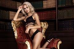 Schöne sexy langhaarige blonde Frau in der schwarzen Wäsche, die im Innenraum aufwirft Die Schönheit des Gesichtes und des Körper Stockbilder