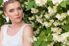 Schöne sexy leichte hübsche Mädchenbraut in einem weißen Kleid, mit empfindlichem Make-up und dem Haar, wenn die Ohrringe von den Lizenzfreie Stockfotografie