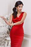 Schöne luxuriöse gut-gepflegte junge Frau in den roten schleichenden Kleiderohrringen mit Diamanten und langem Double des sc Stockfotos