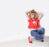 Schöne sexy Mädchenblondine in den Jeans und ein orange T-Shirt, das nahe bei einer weißen Wand im Studio, Modefotografie sitzt Stockbild