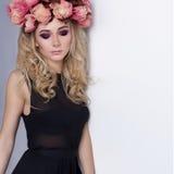 Schöne sexy nette Mädchenblondine im langen Kleid der schwarzen Mode und mit einem Kranz auf seinem Kopf im Studio mit hellem Mak Lizenzfreie Stockfotos