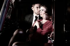 Schöne sexy Paare, gutaussehender Mann im Anzug, Schönheit im roten Kleid, umfassen leidenschaftlich im Weinleseauto lizenzfreie stockfotos