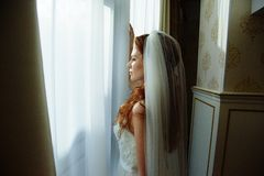 Schöne sexy redhair Dame im eleganten weißen Hochzeitskleid Modeporträt des Modells zuhause Schönheitsfrau, die weit von Wind ste lizenzfreie stockfotografie