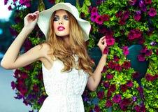 Schöne sexy stilvolle blonde vorbildliche nahe helle Blumen Lizenzfreies Stockfoto