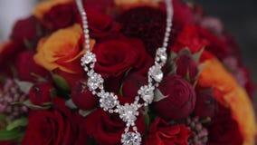 Schöne silberne Halskette der Nahaufnahme mit Steinen liegt auf schickem Heiratsblumenstrauß der Braut, auf dem Goldeheringe sind stock video footage