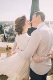 Schöne sinnliche blonde Braut und hübscher Bräutigam, die auf der Dachspitze der alten Kathedrale küsst Lizenzfreie Stockfotos