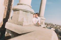 Schöne sinnliche blonde Braut und hübscher Bräutigam, die einander auf Schlossbalkon, Ansicht von unten betrachtend umarmt Lizenzfreies Stockbild