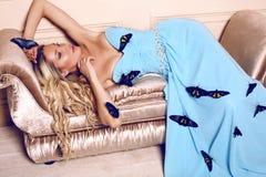 Schöne sinnliche blonde Frau, die mit bunten Schmetterlingen aufwirft Stockbild