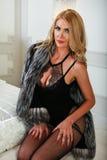 Schöne sinnliche blonde Frau im schwarzen Wäschebodysuit und Pelzmantel, der auf einem Bett sitzt Stockfoto
