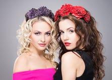 Schöne, sinnliche blonde und tragende der Blume des Brunette gleichkronen Stockfotografie