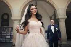 Schöne sinnliche Brunettebraut in der sahnigen Hochzeitskleideraufstellung Stockbilder