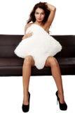 Schöne sinnliche Frau, die auf einem Sofa sitzt Stockbild