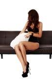 Schöne sinnliche Frau, die auf einem Sofa sitzt Stockbilder
