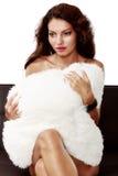 Schöne sinnliche Frau, die auf einem Sofa sitzt Lizenzfreies Stockfoto