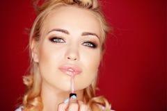 Schöne sinnliche Frau, die Lipgloss anwendet Stockfotografie