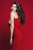 Schöne sinnliche Frau mit geschlossenen Augen im roten Kleid Stockbilder