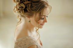 Schöne sinnliche junge blonde Frau, die unten lächelt und schaut Por Stockfotografie