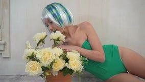 Schöne sinnliche junge Frau im Bodysuit mit der Perücke, die auf dem Boden nahe bei einer Blume in einem Topf aufwirft stock video footage
