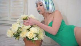 Schöne sinnliche junge Frau im Bodysuit mit der Perücke, die auf dem Boden nahe bei einer Blume in einem Topf aufwirft stock video