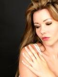 Schöne sinnliche junge Frau mit der Hand auf der Schulter, die Feuchtigkeitscreme anwendet Lizenzfreie Stockfotografie