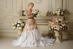 Schöne sinnliche Mädchenblondine im beige Kleid im Innenraum stockbilder