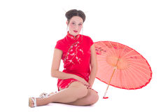 Schöne sitzende Frau auf roten Japaner kleiden mit Regenschirmisolator an Stockfotografie