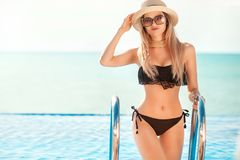 Schöne Sitzfrau im schwarzen Schwimmenanzug und -hut, die auf dem Strand aufwirft Krasnodar Gegend, Katya stockbilder