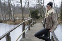 Schöne skandinavische blonde junge Frau, die auf Brücke in der schwedischen Winterlandschaft steht Glückliches Lächeln Stockbild