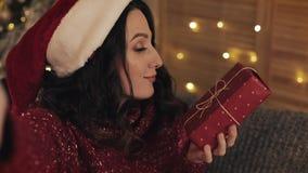 Schöne smilling Frau, die zu Hause selfie Fotos auf Smartphonekamera mit Geschenk nahe Weihnachtsbaum macht stock video