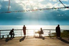 Schöne Sommerzeit, ruhiges szenisches des Seeufers an der Dämmerung, buddhistische Mönche und Leute, die im Sonnenunterganglicht, stockfotografie