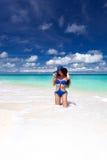 Schöne Sonnenbräunefrau, die auf tropischem Strand aufwirft lizenzfreies stockbild