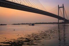 Schöne Sonnenuntergangfarbe auf Fluss Hooghly mit der Brücke Vidyasagar Setu am Hintergrund Stockbilder
