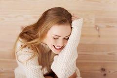 Schöne sorglose junge zufällige Frau, die auf dem Boden sitzt. Stockfoto