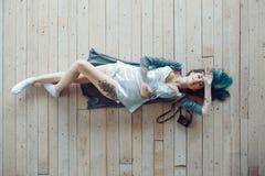 Schöne sorglose junge zufällige Frau, die auf dem Bretterboden liegt Lizenzfreies Stockfoto