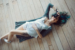 Schöne sorglose junge zufällige Frau, die auf dem Bretterboden liegt Stockbilder