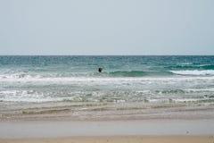 Schöne spanische Küstenlinie: Badendes Frauenschattenbild, Strand, Meer, Wellen mit weißem Kamm lizenzfreies stockbild