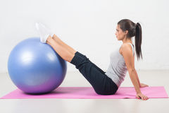Schöne Sportfrau, welche die Eignungsübung, dehnend auf Ball tut aus Pilates, Sport, Gesundheit Stockfotografie