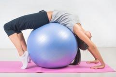 Schöne Sportfrau, welche die Eignungsübung, dehnend auf Ball tut aus Pilates, Sport, Gesundheit Stockbild