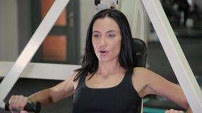 Schöne sportliche Brunettefrau wird auf einem Simulator für die Muskeln des Kastens und der Arme engagiert Enthalten Sie Steigung stock footage