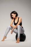 Schöne sportliche Dame, die auf einem Eignungsball sitzt Lizenzfreie Stockfotografie