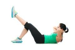 Schöne sportliche Frau, die Übung auf dem Boden tut lizenzfreies stockbild