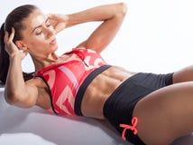 Schöne sportliche Frau, die Übung für ABS auf weißem backgroun tut Lizenzfreie Stockfotografie