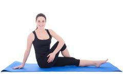 Schöne sportliche Frau, die auf dem Boden lokalisiert auf Weiß sitzt Stockfoto