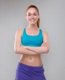 Schöne sportliche Frau, die mit den Armen gekreuzt lächelt Stockfoto