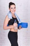 Schöne sportliche Frau mit der Yogamatte, die über weißem Ziegelstein w steht Stockfotografie