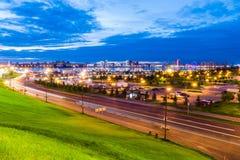 Schöne Stadtlandschaft mit einer Straße, einem Park und einem See bei Sonnenuntergang Lizenzfreie Stockbilder