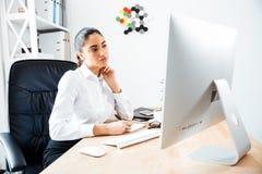 Schöne starke Geschäftsfrau, die Anmerkungen macht und Bildschirm betrachtet Lizenzfreies Stockfoto